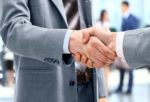 two businessmen shaking hands with other business people in the background